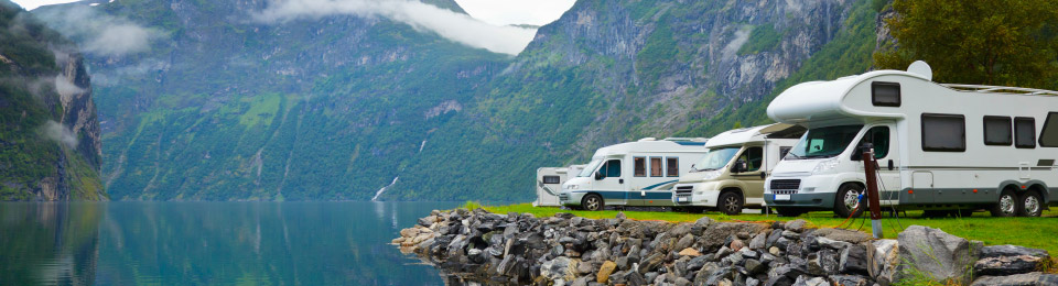 RVs along the banks of placid lake in mountains